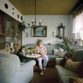 Eine ältere Frau sitzt in ihrem Wohnzimmer