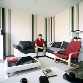 Ein junger Mann sitzt auf dem Sofa in seinem Wohnzimmer