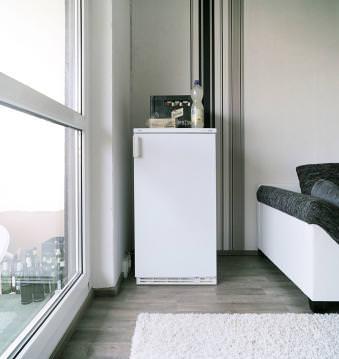 Ein Kühlschrank steht in einer Ecke am Fenster