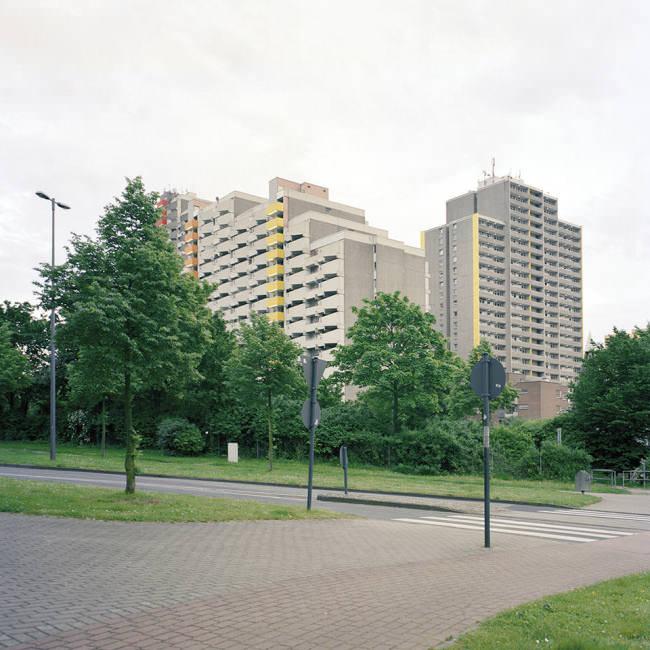 Blick auf einen Wohnblock hinter Bäumen