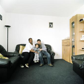 Eine junge Familie auf dem Sofa in ihrem Wohnzimmer