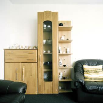 ein Wandschrank und zwei schwarze Sessel