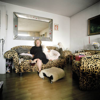 Eine ältere Dame mit ihren zwei Schoßhündchen auf einem Sofa mit Leopardenmuster