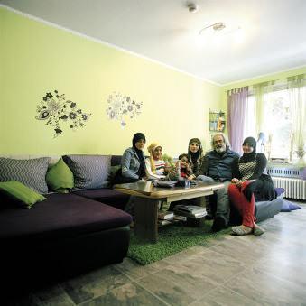 Eine Famile auf dem Sofa in ihrem Wohnzimmer