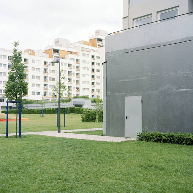 Blick über den Rasen auf eine Fluchttür in einer Wohnsiedlung