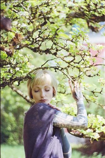 Blonde Frau in einem Magnolienbaum.