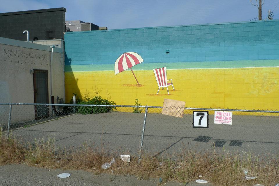 Schiefer Zaun vor Wand, auf der ein Strand aufgemalt wurdde.