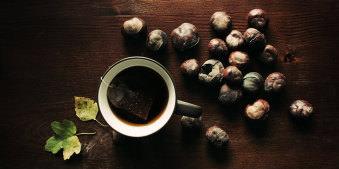 Eine Tasse Tee, einige Kastanien und zwei gelbgrüne Blätter auf braunem Holz.