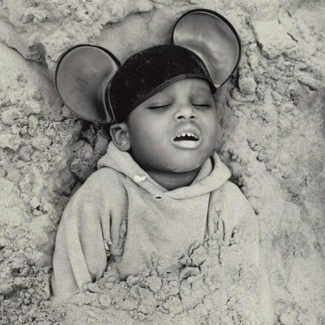 Ein Junge ist in Sand eingegraben.