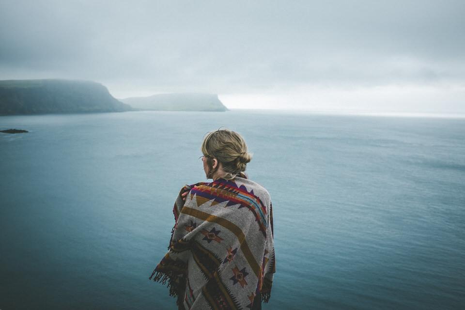 Eine Frau in ein Tuch gehüllt steht mit dem Rücken zur Kamera vor einem nebligen Meer.