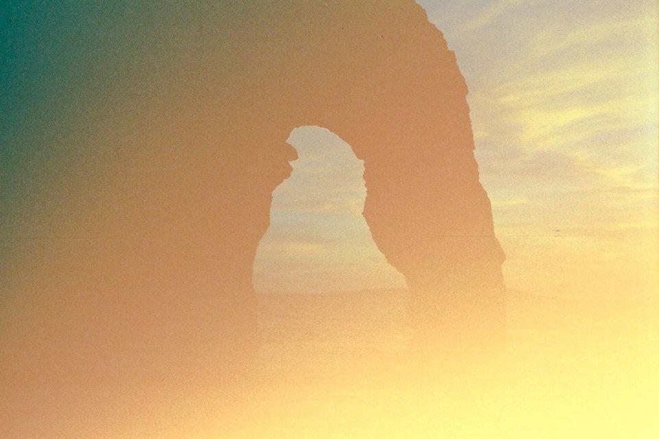 Ein Felsen am Meer, von einem Lightleak erhellt.
