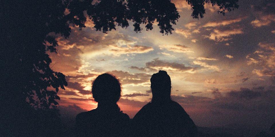 Zwei Personen schauen sich einen malerischen Sonnenuntergang an.