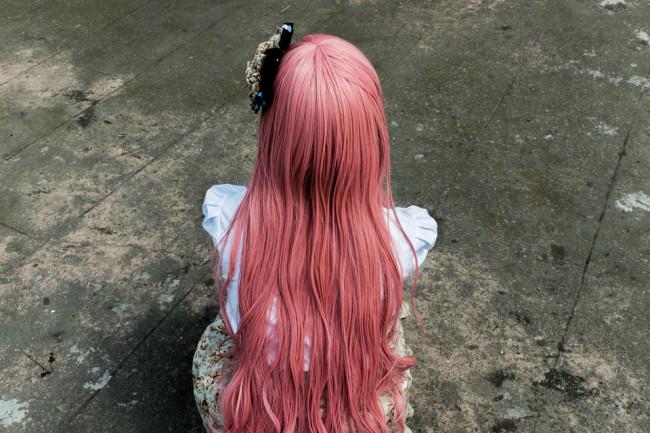 Eine Frau mit langen rosa Haaren in Rückansicht.
