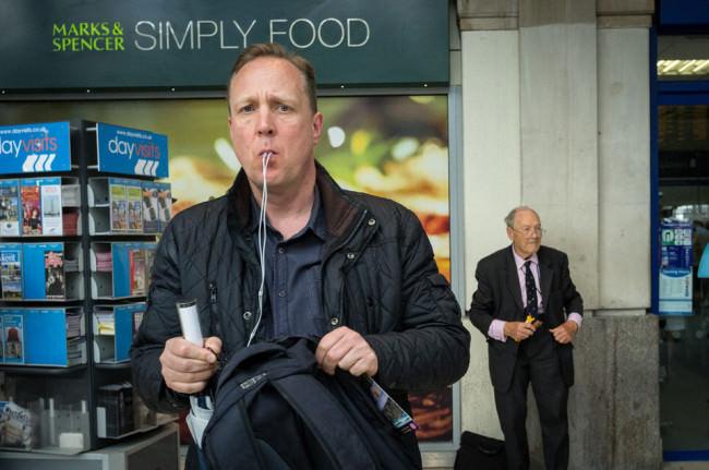 Ein Mann steht vor einem Geschäft, die Kabel seiner Kopfhörer laufen aus seinem Mund.