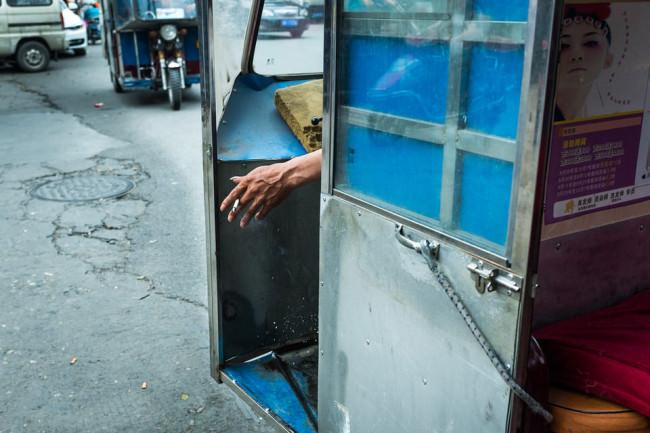 Aus einem Führerhäuschen lugt eine Hand mit Zigarette.