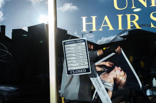 Ein Mann hängt hinter einer Fensterscheibe ein Poster auf.
