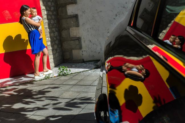 Eine Frau hält ein Kleinkind auf dem Arm und spiegelt sich im Lack eines Autos.