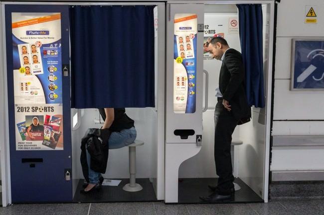 Eine Frau sitzt in einem Fotoautomaten, im nächsten Automat hinter ihr steht ein Mann, der auf sie zu schauen scheint.
