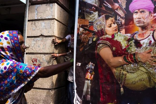Personen greifen um eine Ecke und ein buntes Plakat mit weiteren Menschen ragt ins Bild.