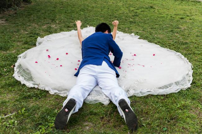 Ein Mann in Rückansicht liegt auf dem Brautkleid einer Frau.