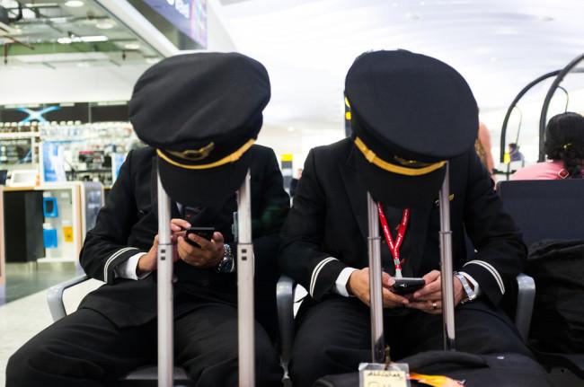 Die Mützen zweier Piloten hängen auf den Ausziehgriffen zweier Koffer, hinter denen die zwei Männer sitzen.