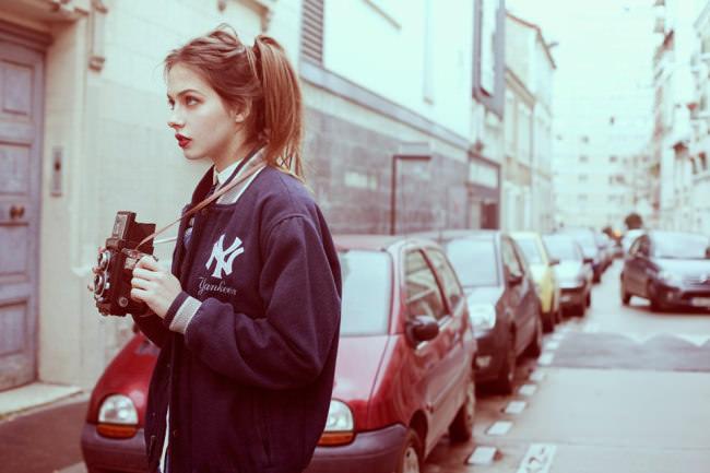 Eine Frau mit rotem Lippenstift hält eine alte Kamera in der Hand.