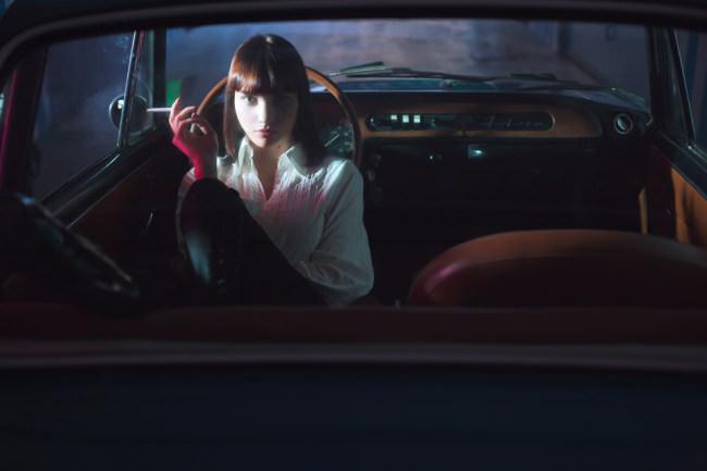 Eine Frau sitzt im Auto auf dem Fahrersitz und schaut uns an.