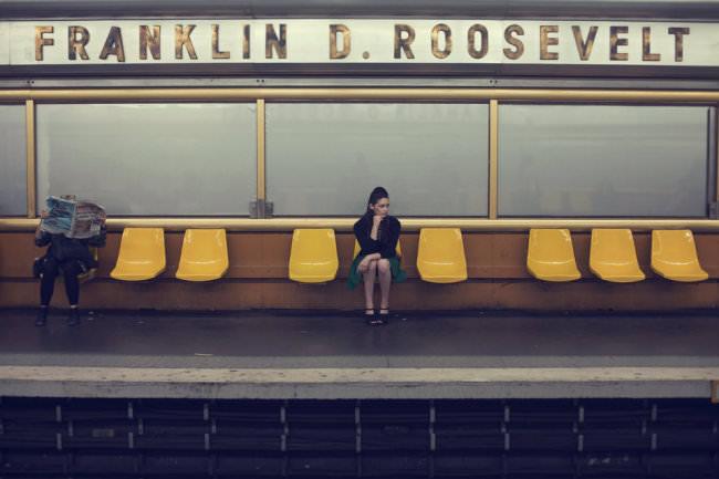 Eine Frau sitzt auf gelben Plastikstühlen und wartet auf den Zug.