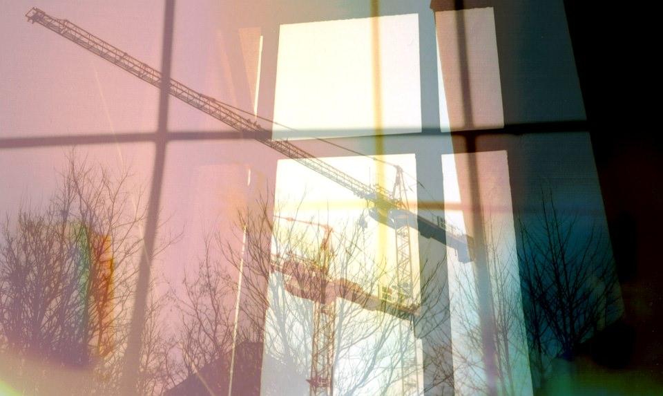 Mehrfachbelichtung aus einem Fenster, hinter dem man Krane sieht.