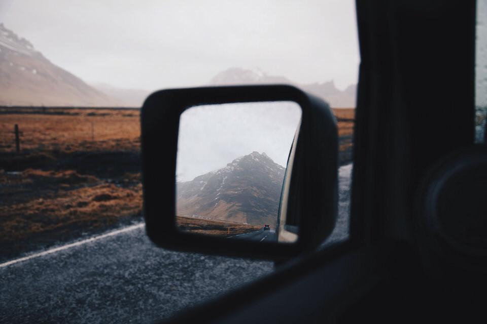 Vernebelte Berge im Rückspiegel eines Autos.