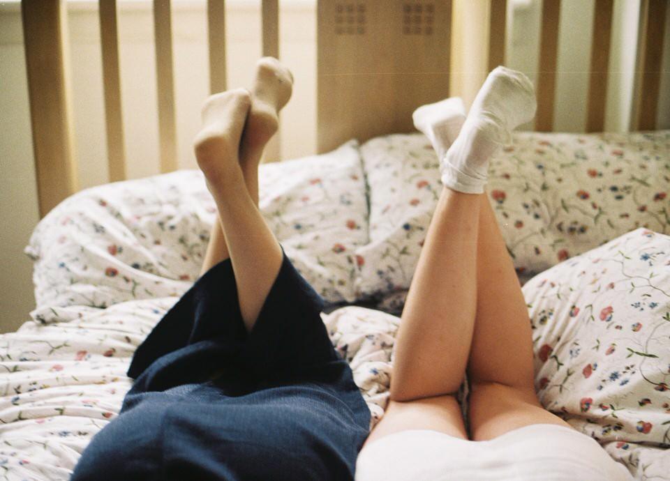 Zwei Beinpaare in einem Bett.