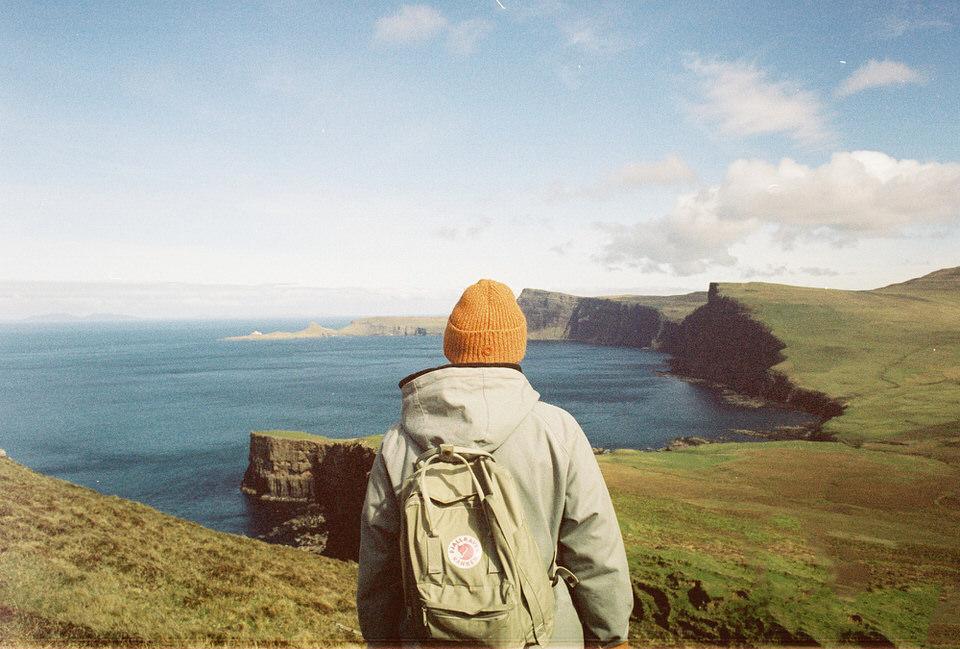 Ein Wanderer steht vor einer Landschaft.