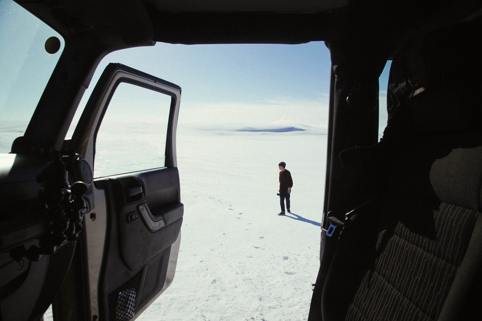 Durch die Tür eines Autos ist ein Mensch im Schnee zu sehen.