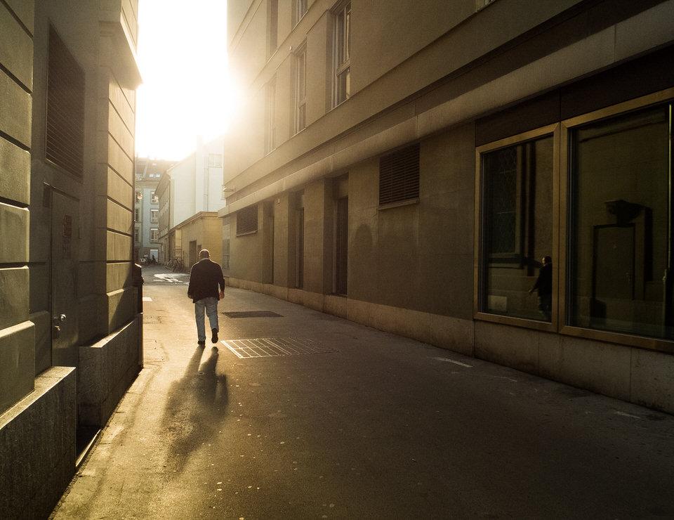 Ein Mann läuft eine Straße im Gegenlicht entlang.