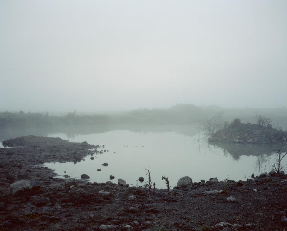 Düstere Morgenlandschaft mit Blick auf vernebelten See