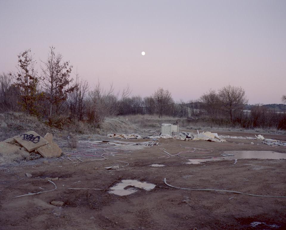 Der Mond steht vor einer von Müll beladenen Landschaft