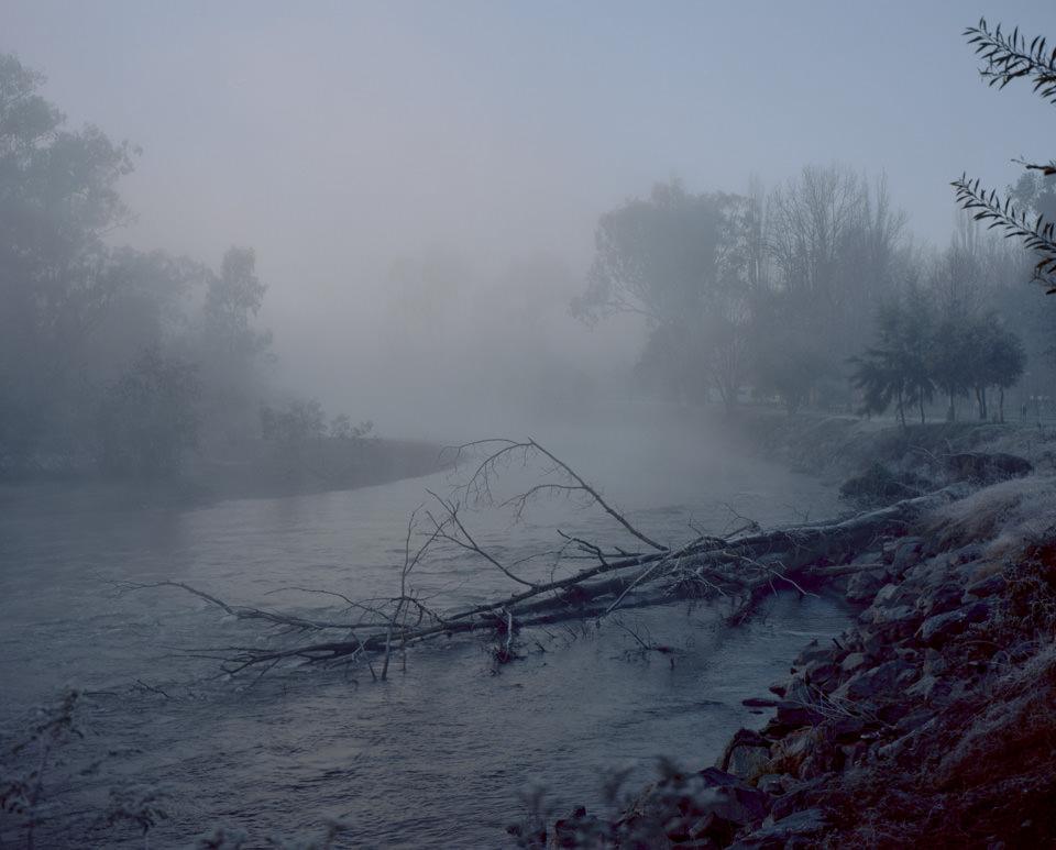Blick auf eine dunkel-vernebelte Flusslandschaft