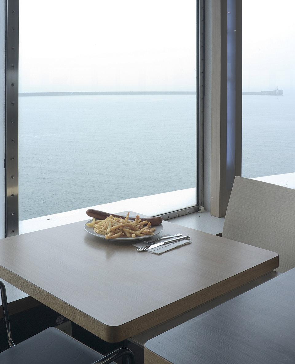 Ein Teller mit Pommes und Bratwurst auf einem Tisch am Fenster mit Blick aufs Wasser.