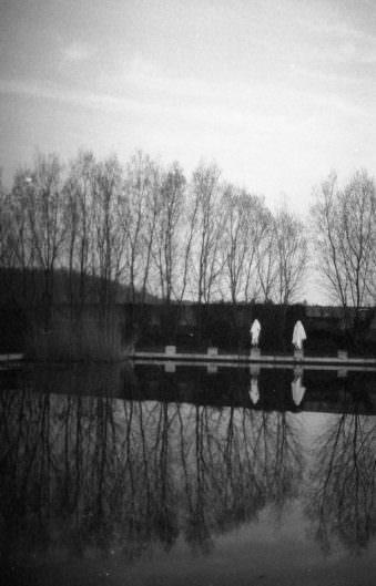 Zwei Menschen am Rand eines Schwimmbeckens.