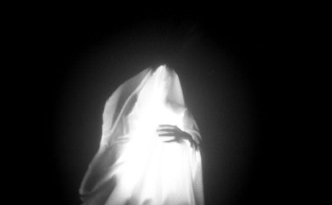Ein Mensch unter einem Laken leuchtet und Du siehst die Hand.