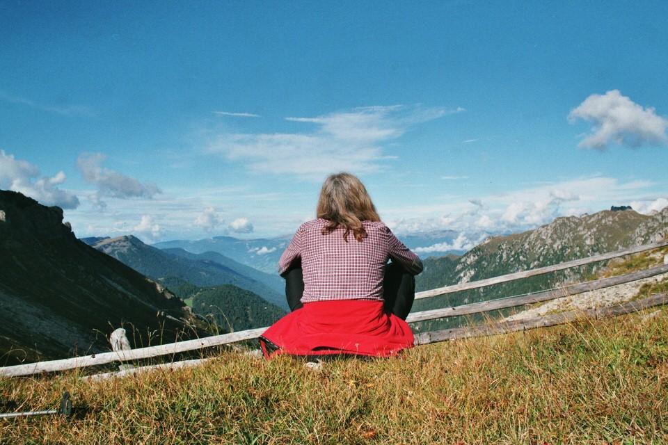 Eine Frau sitzt mit dem Rücken zur Kamera und betrachtet die Landschaft.