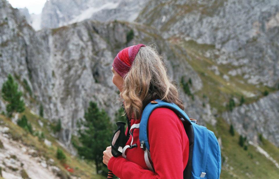 Eine Frau mit Wanderstöcken und Rucksack von der Seite.