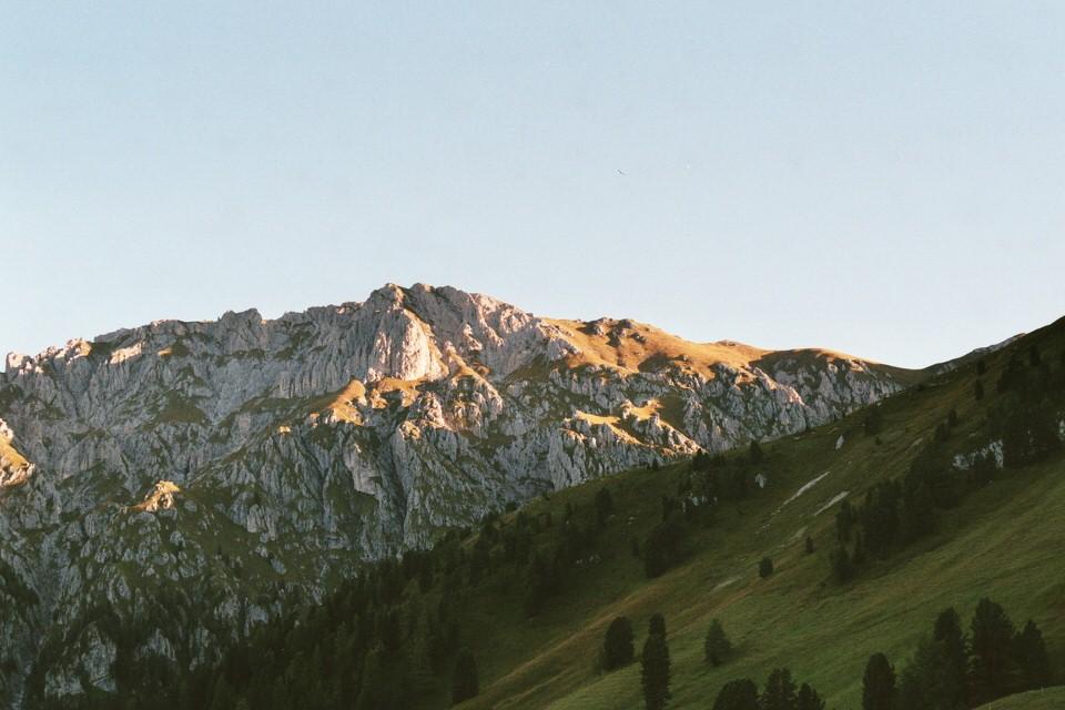 Berge im Hintergund. Wiese im Vordergrund.