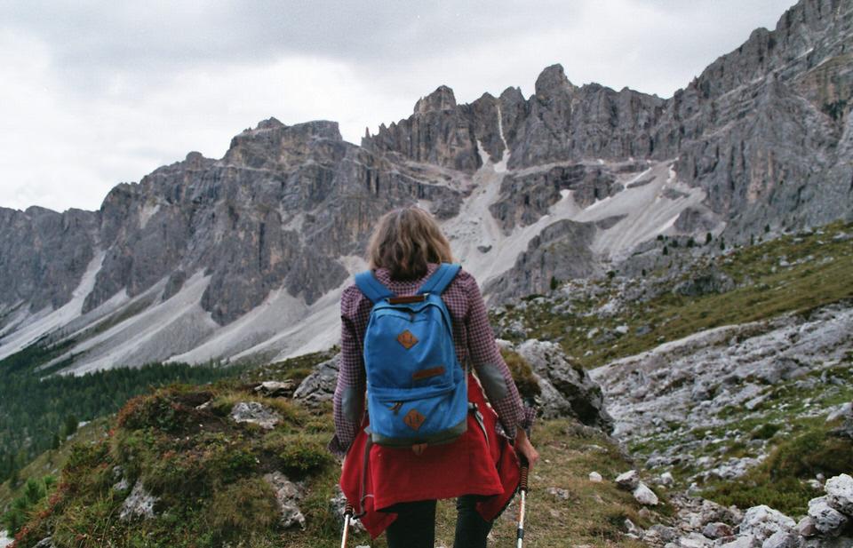 Frau mit Wanderstöcken in Alpenlandschaft.