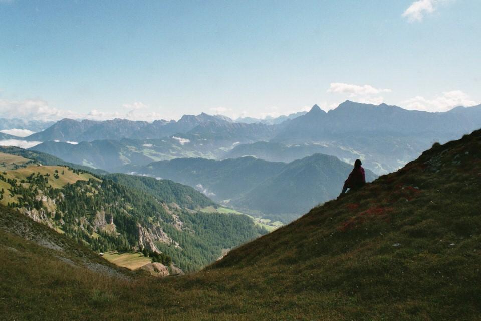 Landschaftsaufnahme der Alpen. Ein Mädchen sitzt am Rand auf einem Hügel.