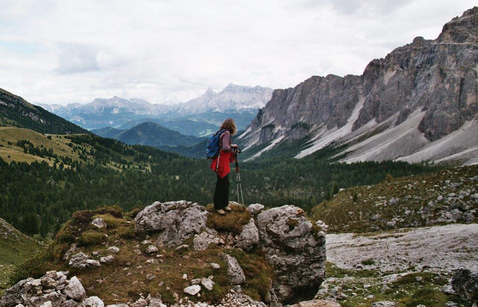 Frau auf Felserhöhung vor Alpenlandschaft.