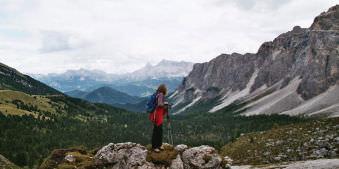 Wanderin auf einem Hügel blickt in die Alpenlandschaft.