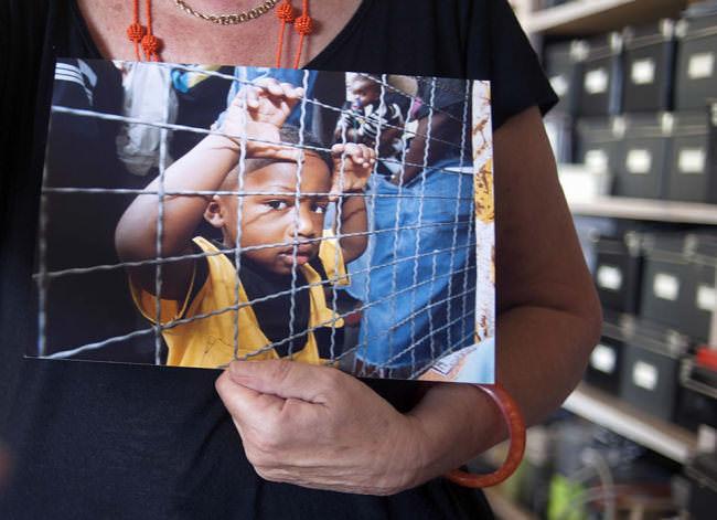 Ein dunkelhäutiger Junge steht in der Anlufstelle für Asylsuchende an einem Zaun und schaut verlegen in die Kamera.