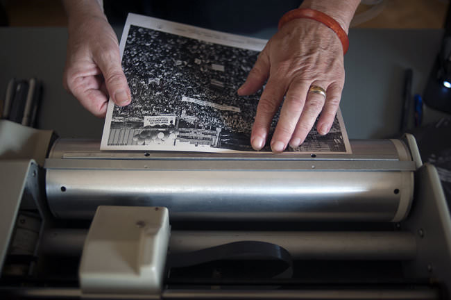Zwei Hände spannen einen Fotoabzug auf die Walze eines Bildfaxes.