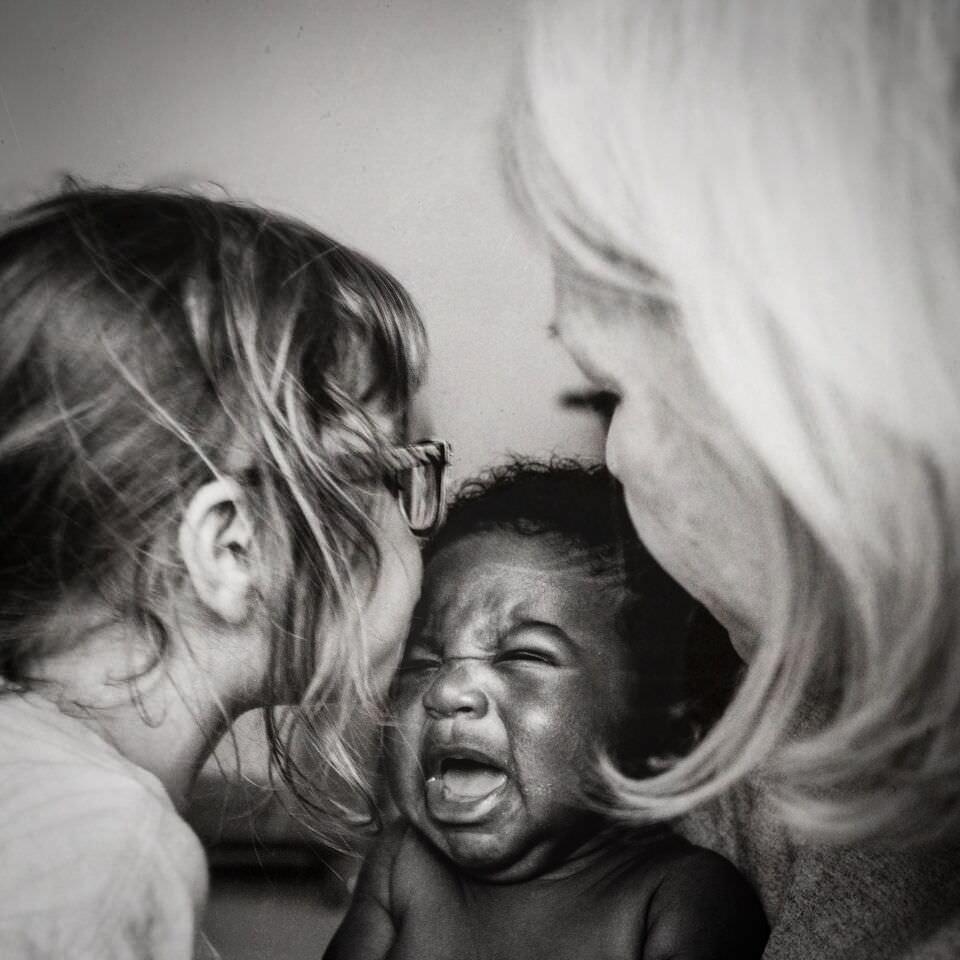 Zwei Mädchen umringen ein schreiendes Baby.